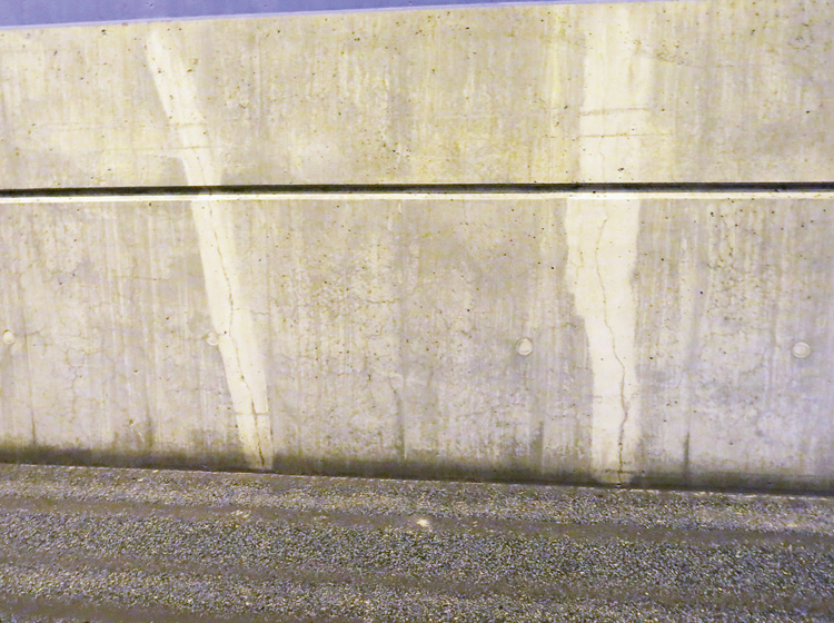 Kraftig sprickbildning och krackelering i betongsockel, cirka tio år i drift. Notera även hur kloridhaltigt vatten från vägbanan sugs upp cirka 200 mm i sprickorna.