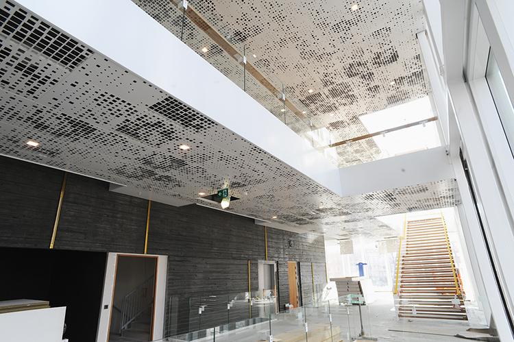 Foajée i Malmö Live, med dekorativa ljuddiffuserade betongelement och perforerat plåtundertak med mineralullsabsorbent på ovansidan.